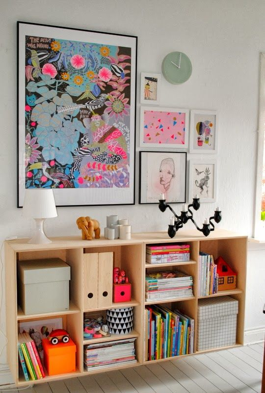 a bold gallery wall with bright posters and watercolors in black and white frames to give more color to the space