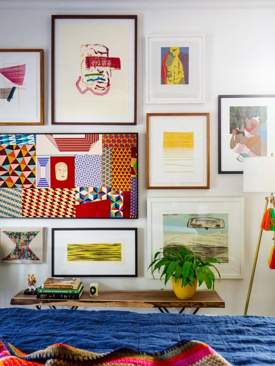 a bold gallery wall with colorful artworks, posters and prints and mismatching frames is a maximalist idea to rock