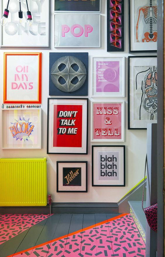 a bold pop art gallery wall with various posters and prints in bold colors is a very bright and fun idea for a colorful space