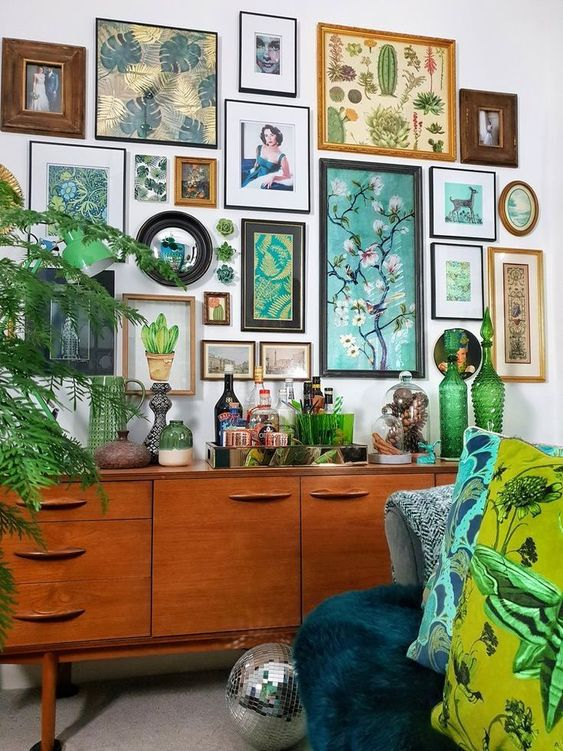 a botanical gallery wall with various art in mismatching frames and even faux succulents right on the wall is wow
