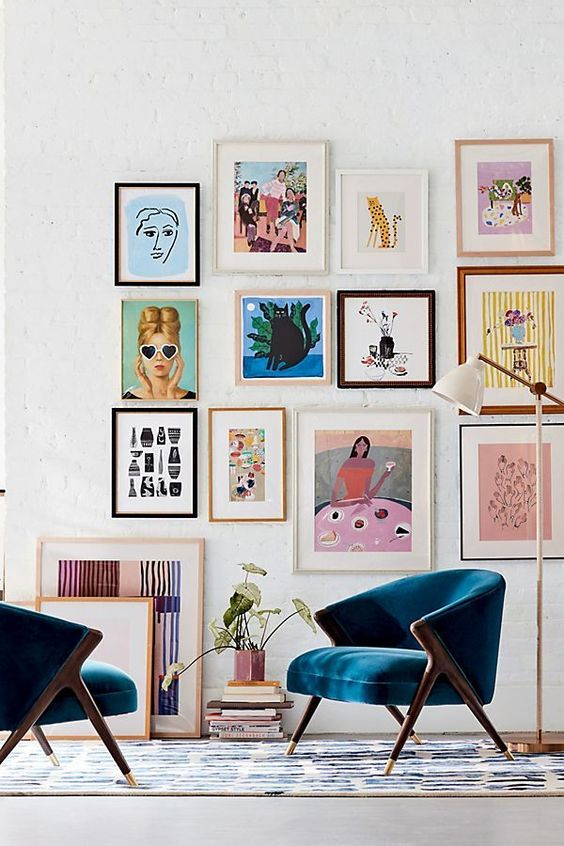 a bright and colorful gallery wall with mismatching frames, colorful posters and artworks and fun primitive artworks