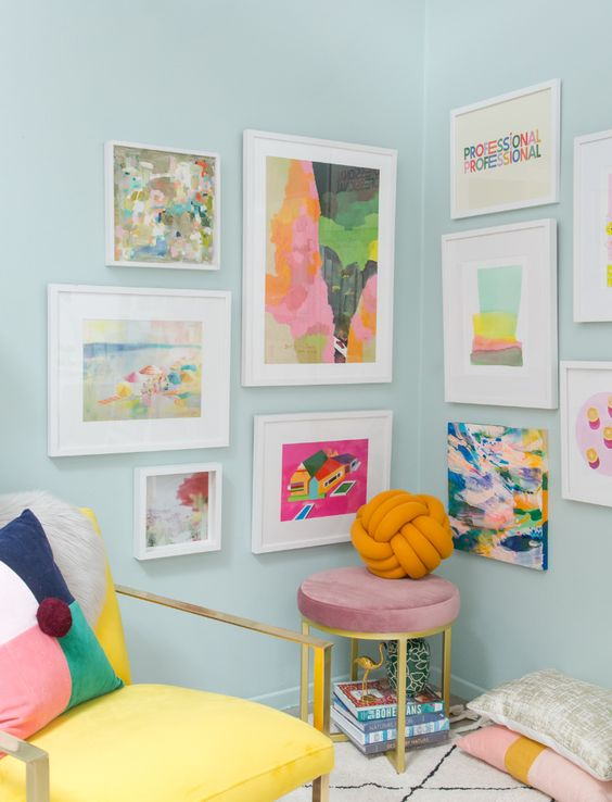 a bright and fun gallery wall taking two walls, with colorful abstract art and white frames