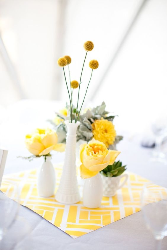 a bright and fun spring centerpiece with milk vases, yellow blooms, succulents and greenery