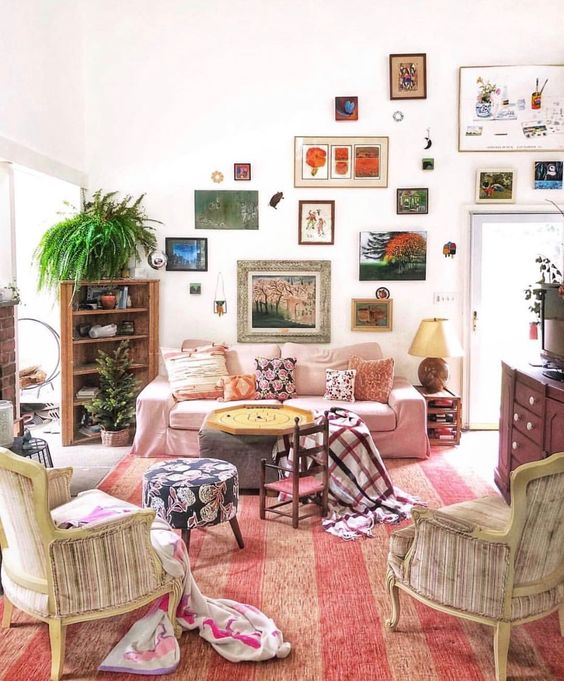 a bright eclectic gallery wall with mismatching frames climbing up the wall and going over the doorway is a very creative idea