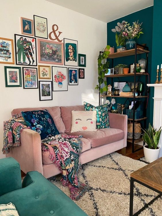a bright free form gallery wall with mismatching frames and colorful artworks including floral ones plus textiles with the same patterns