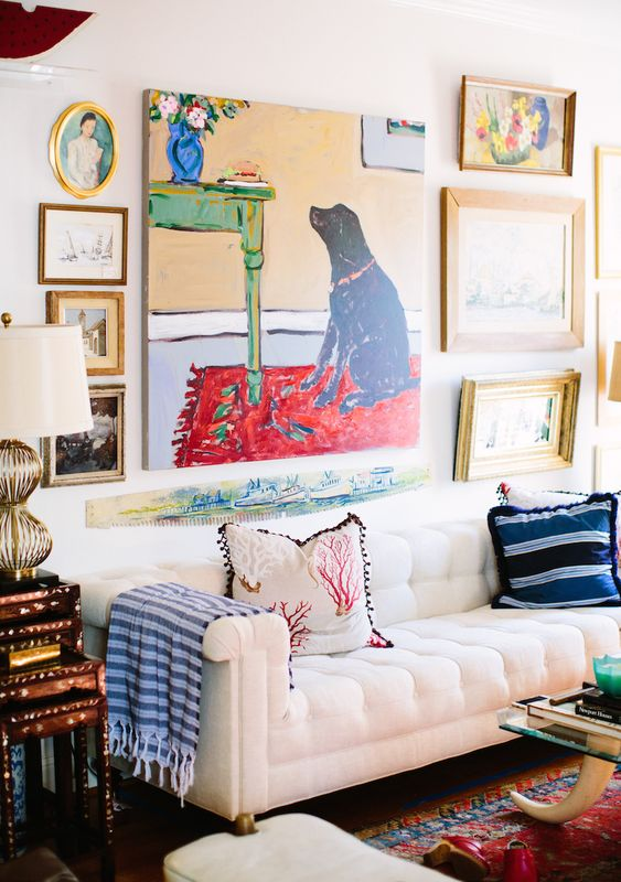 a bright gallery wall with a bold non-framed artwork in the center and some mismatching artworks around