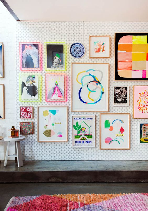 a bright gallery wall with abstract artworks and prints, with neon ligth frames and usual ones for a funky look