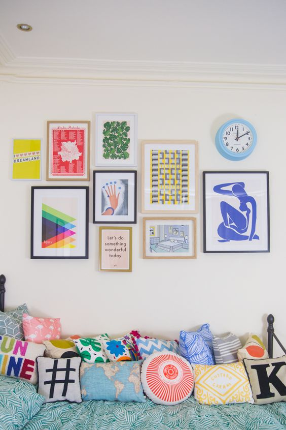 a bright gallery wall with bold posters and prints in mismatching frames will add a cool and cheerful touch to the space