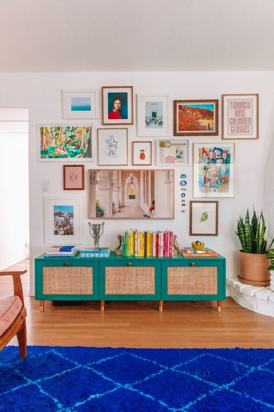 a bright gallery wall with mismatching frames and bold artworks, with a free form and a hanging with blue stones