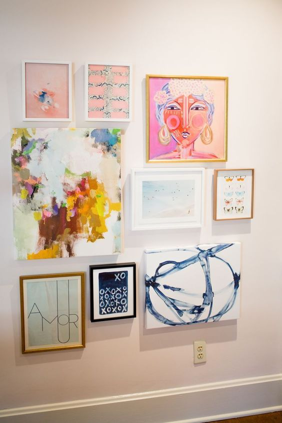 a bright gallery wall with mismatching frames and bright artworks is a bold and cool idea for a bright space