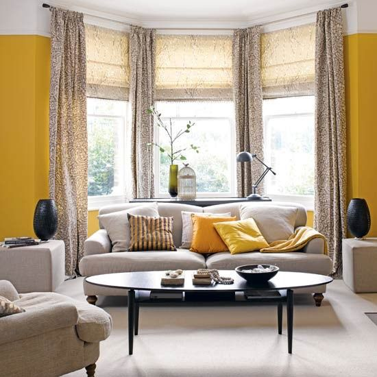 a bright grey and yellow living room with a bow window done with printed curtains, grey seating furniture and a refined table