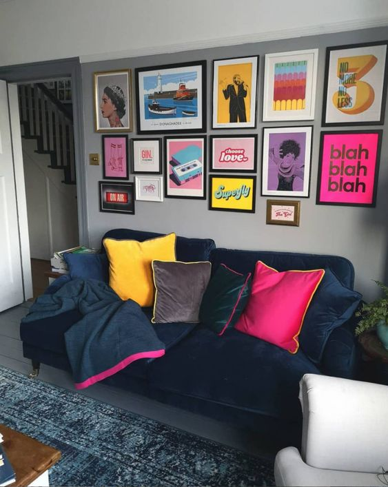a bright pop art gallery wall with posters and prints in various colors united with the same style frames for a bold touch in a moody living room