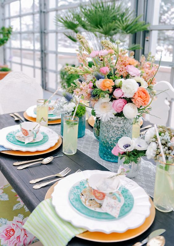 a bright spring centerpiece of a blue vase, white and colorful blooms and greenery is a cool idea