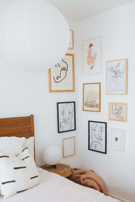 a catchy gallery wall covering the corner with blonde wood, white and black frames, white matting and some abstract art