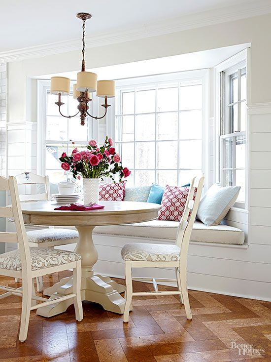 a charming cottage dining space with a bow window, a windowsill seating, a round table and neutral chairs plus a vintage chandelier