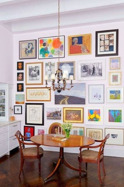 a cheerful and colorful free form gallery wall with mismatching frames and black and white and bold rainbow artworks is a fun idea