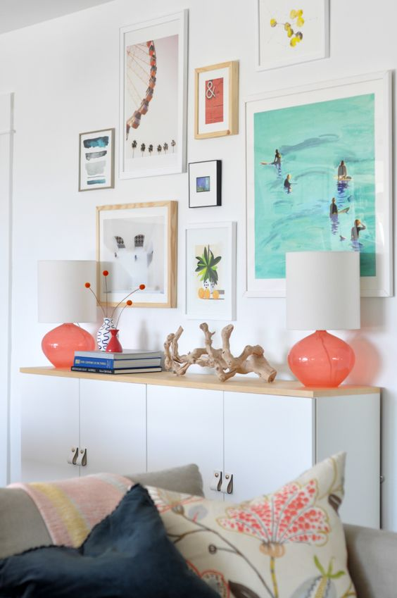 a cheerful vacation-inspired gallery wall with mismatching frames and bright prints and artworks is bold and fun