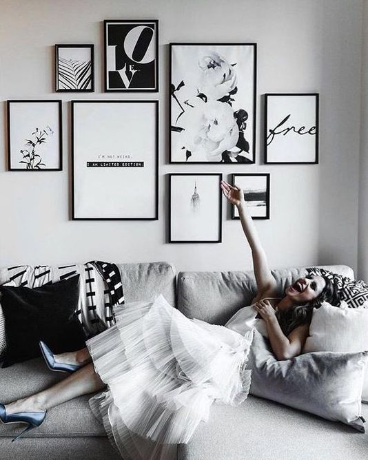 a chic black and white free form gallery wall with thin black frames and black and white art just wows