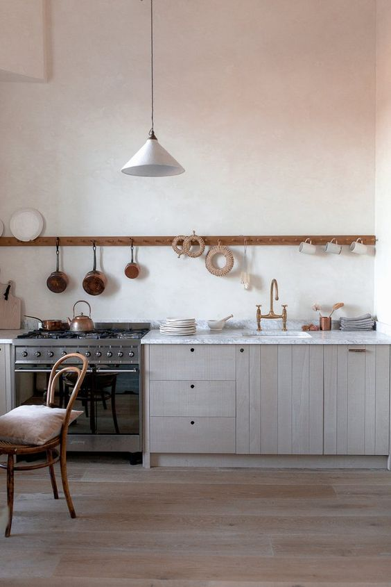 a chic blonde wood one wall kitchen with a white stone countertop and a long holder with mugs and pans
