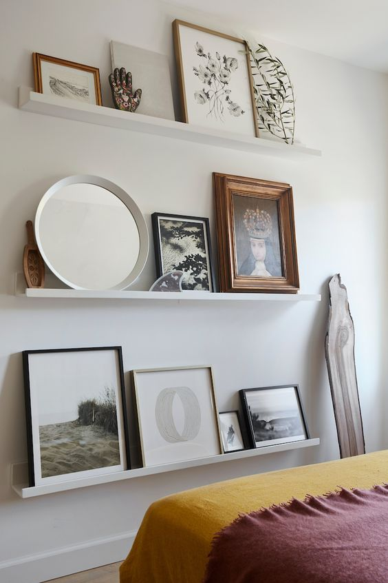 a chic contemporary gallery wall with white ledges, various artworks, a round mirror, some figurines and a greenery branch