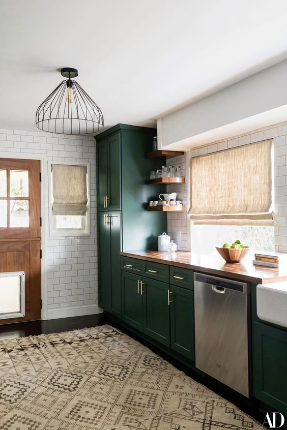 a chic dark green farmhouse kitchen with a buctcherblock countertop, woven shades and metal pendant lamps plus a boho rug