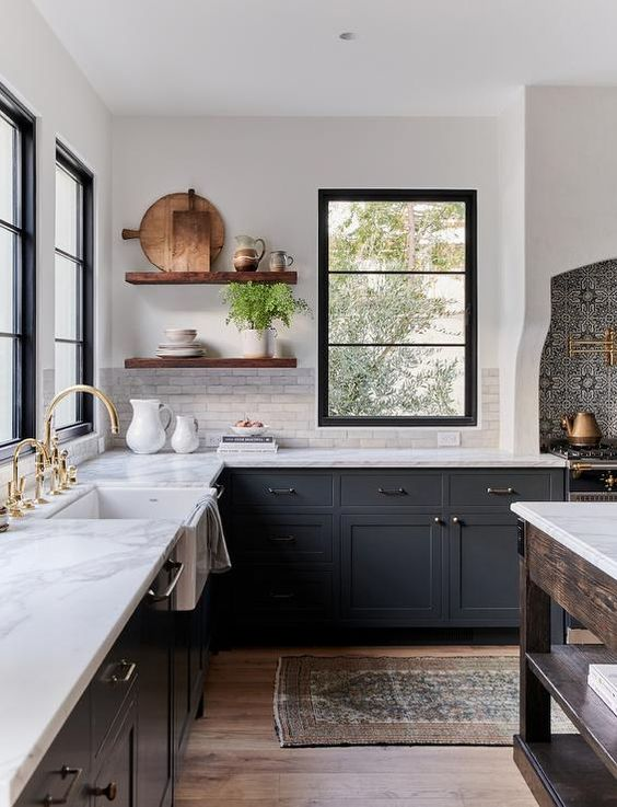 a chic dark grey farmhouse kitchen with white quartz countertops and a white marble tile backsplash, stained floating shelves and mixed metals