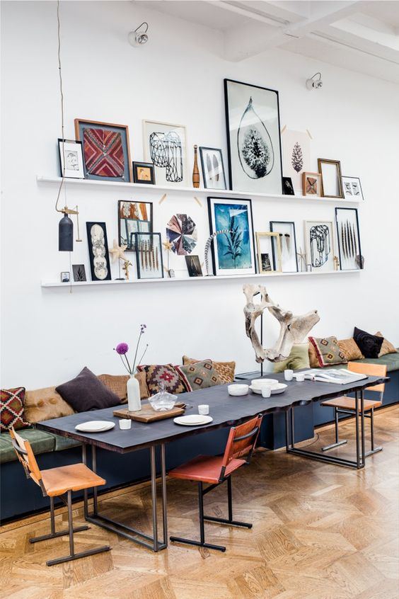 a chic dining room with a boho feel and a bright gallery wall done with white ledges and colorful artworks and decorations that enlivens the space