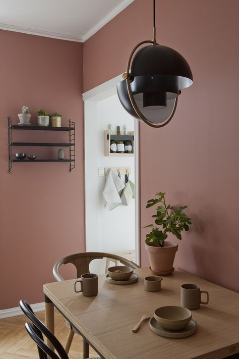 a chic dining room with mauve walls, a wooden table and mismatching chairs, a pendant lamp and an open shelving unit
