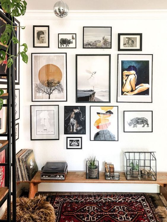 a chic free form gallery wall with thin black frames, white matting and various types of art presented