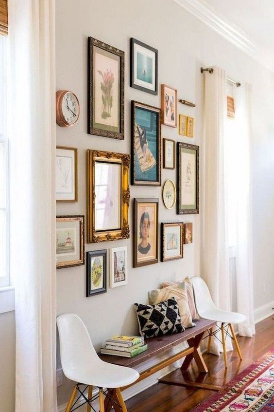 a chic free form gallery wall with vintage frames and colorful art of various kinds plus a clock is catchy