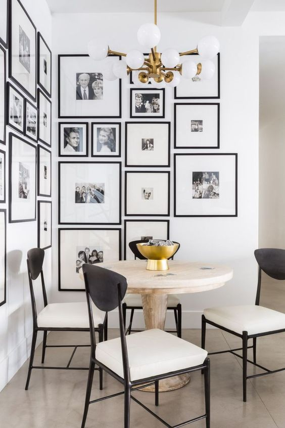 a chic gallery wall with black and white photos and in matching black frames accents this dining corner