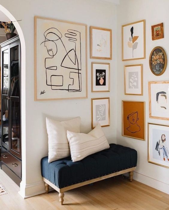 a chic gallery wall with gold and blonde wood frames and abstract art of various kinds