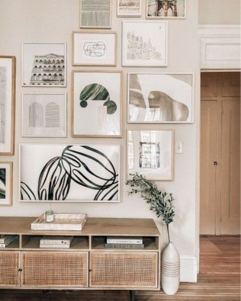 a chic gallery wall with mismatching blonde wood and white frames and muted color art and prints is stylish