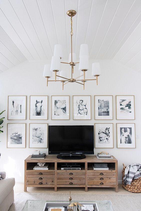 a chic gallery wall with thin gold frames, white matting and black and white photos framing the TV is cool