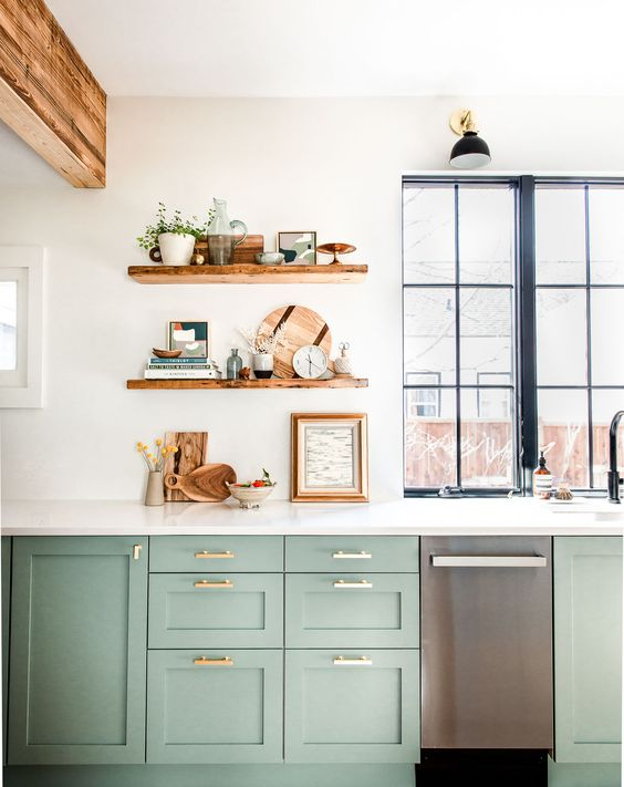a chic green kitchen in farmhouse style, a white stone countertop and open shelves, wooden beams and a window with a black frame