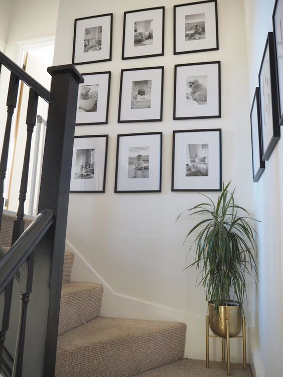 a chic grid gallery wall with matching black frames and black and white photos is a lovely way to display your family pics
