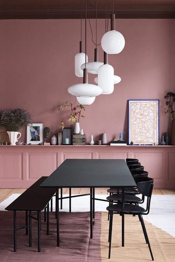 a chic mauve dining room with black furniture and a long shelf showing off various vases and decor plus a cluster of pendant lamps