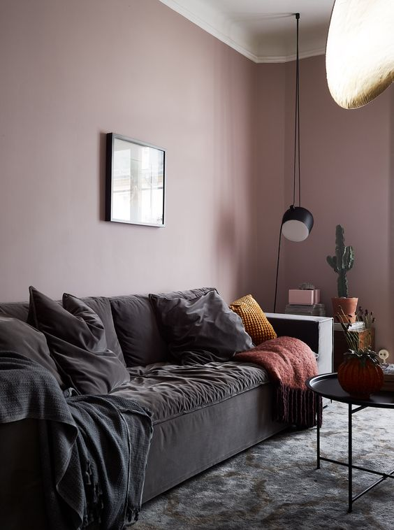 a chic mauve living room with black furniture for more drama, potted plants and pendant lamps looks wow