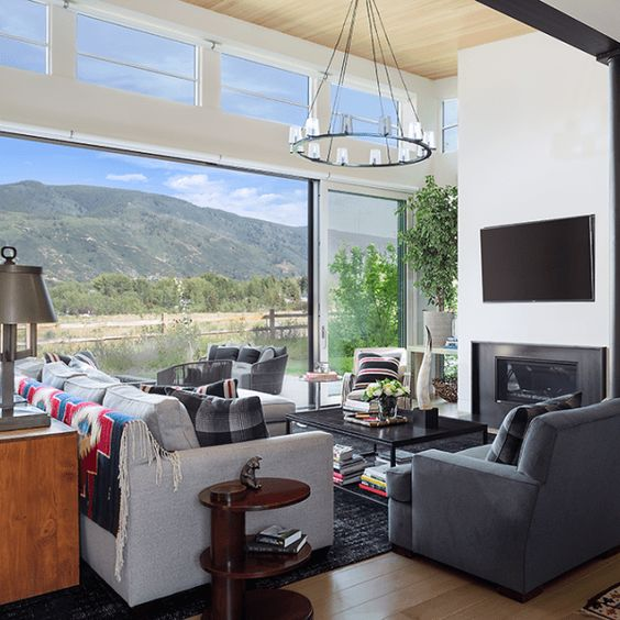 a chic modern living room with comfy furniture and a built-in fireplace, a glazed wall and additional clerestory windows to fill the space with light