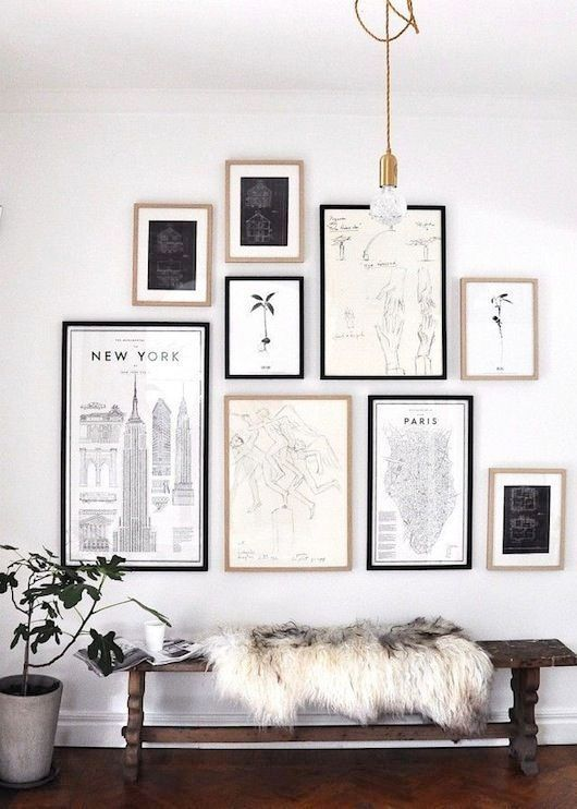 a chic monochromatic gallery wall with black and blonde wood frames, black and white artworks and prints