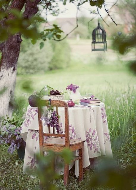 a chic rustic dining area with a table and a chair placed under the tree, a candle lantern and a pretty floral tablecloth