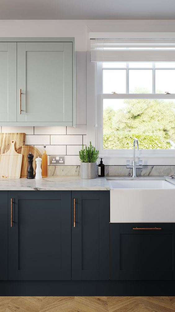a chic two tone kitchen with light green and graphite grey shaker cabinets, a white subway tile backsplash and white marble countertops