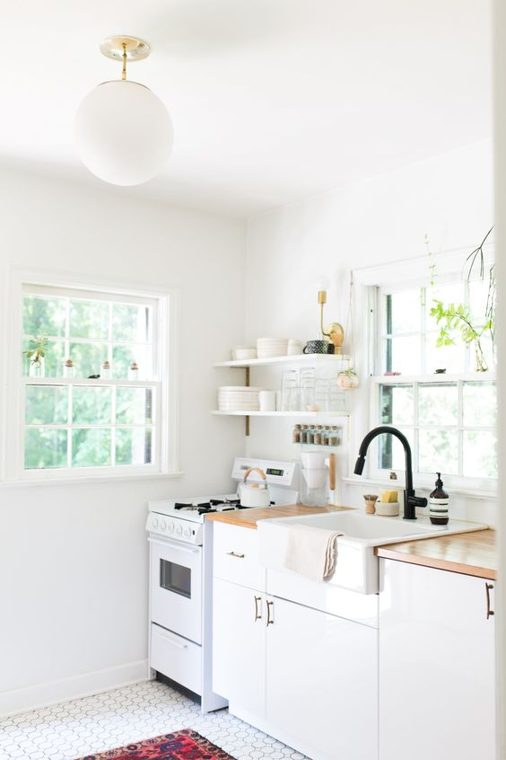 a chic white one wall kitchen with butcherblock countertops and black fixtures, a tile floor and a bold rug
