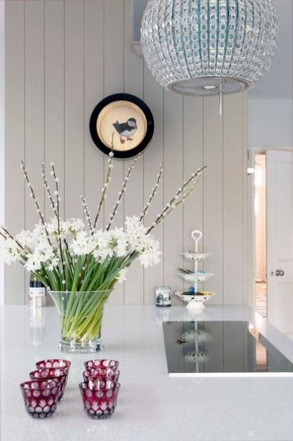 a clear vase with white blooms and willow is a lovely and fresh spring centerpiece to enjoy
