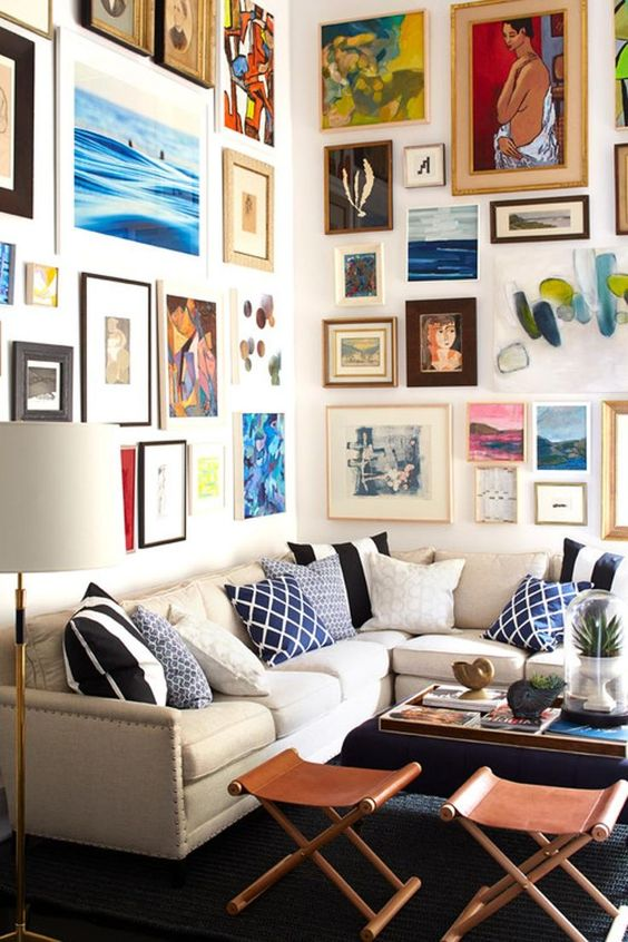 a colorful gallery wall taking two walls with mismatching frames and super bold artworks in various styles and in various colors