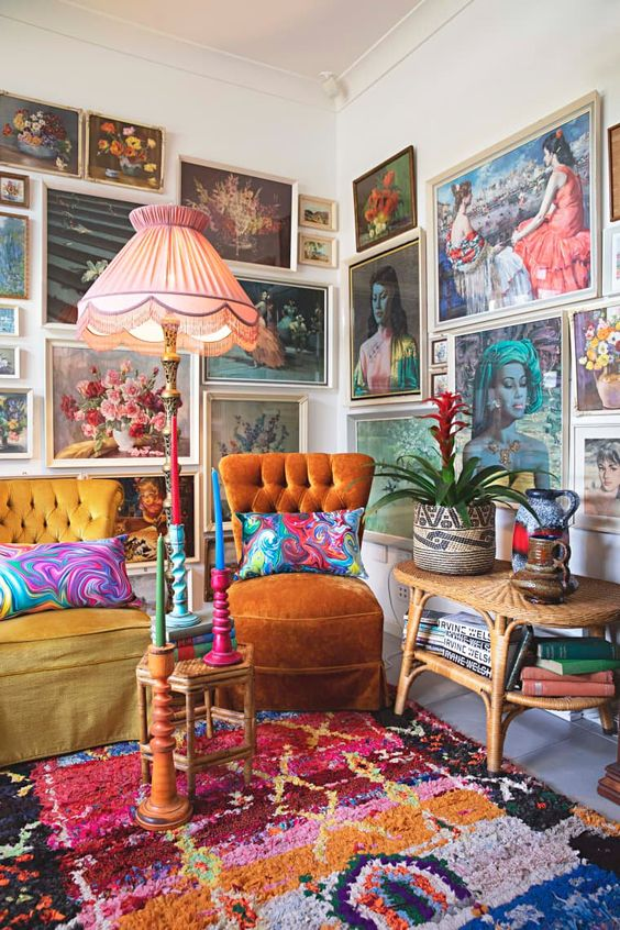 a colorful gallery wall taking two walls, with vintage paintings in neutral frames, with portraits and botanicals is amazing