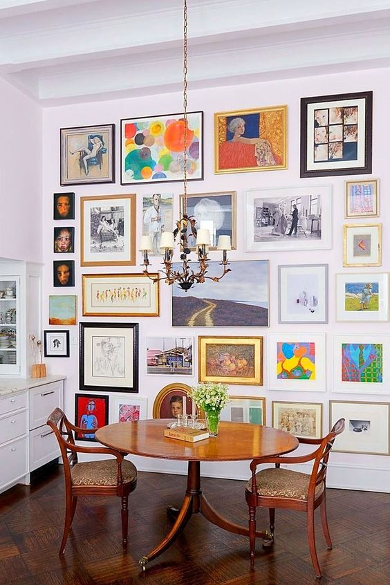 a colorful gallery wall with mismatching vintage frames, with and without mats, with art in various bright colors