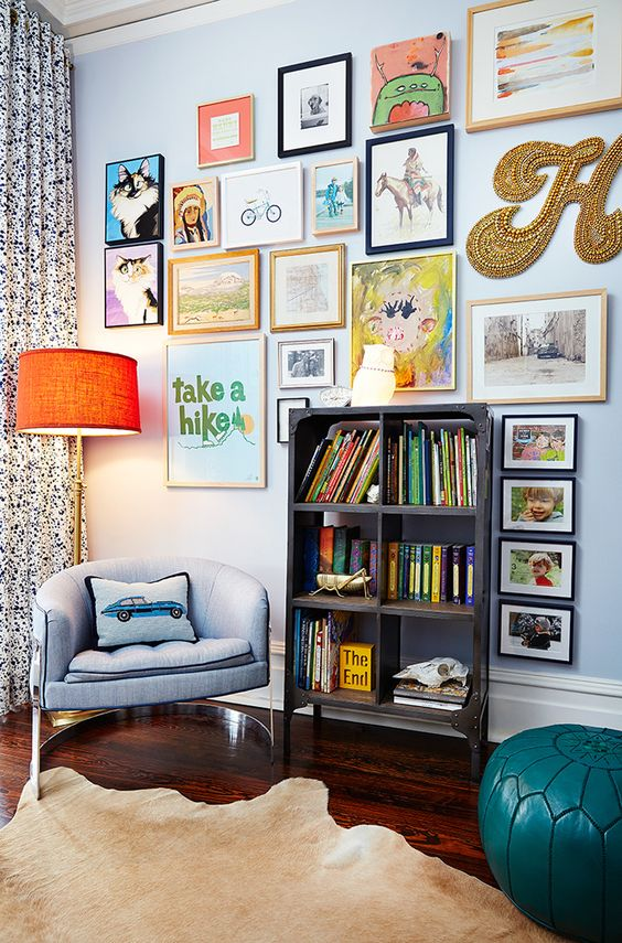 a colorful gallery wlal with mismatching frames, a creative form, a gold bead monogram and some posters is fun