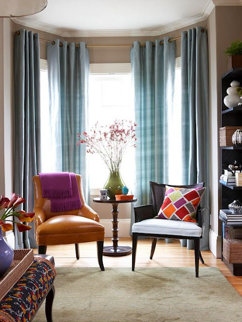 a colorful nook with a bow window, blue plaid curtains, colorful chairs and pillows plus a round table