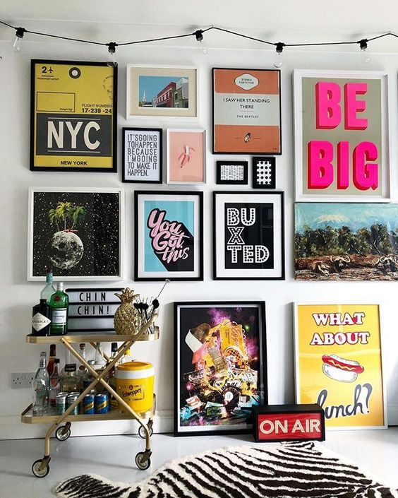 a colorful pop art gallery wall in various colors - posters for fun and with black and white frames is a bold idea
